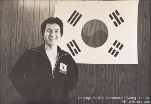 Photo: Master Lee stands proudly in front of the Korean Flag.
